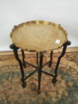 A brass tea tray table with scalloped edging, engraved in a Japanese theme, supported on a 6 arm/leg