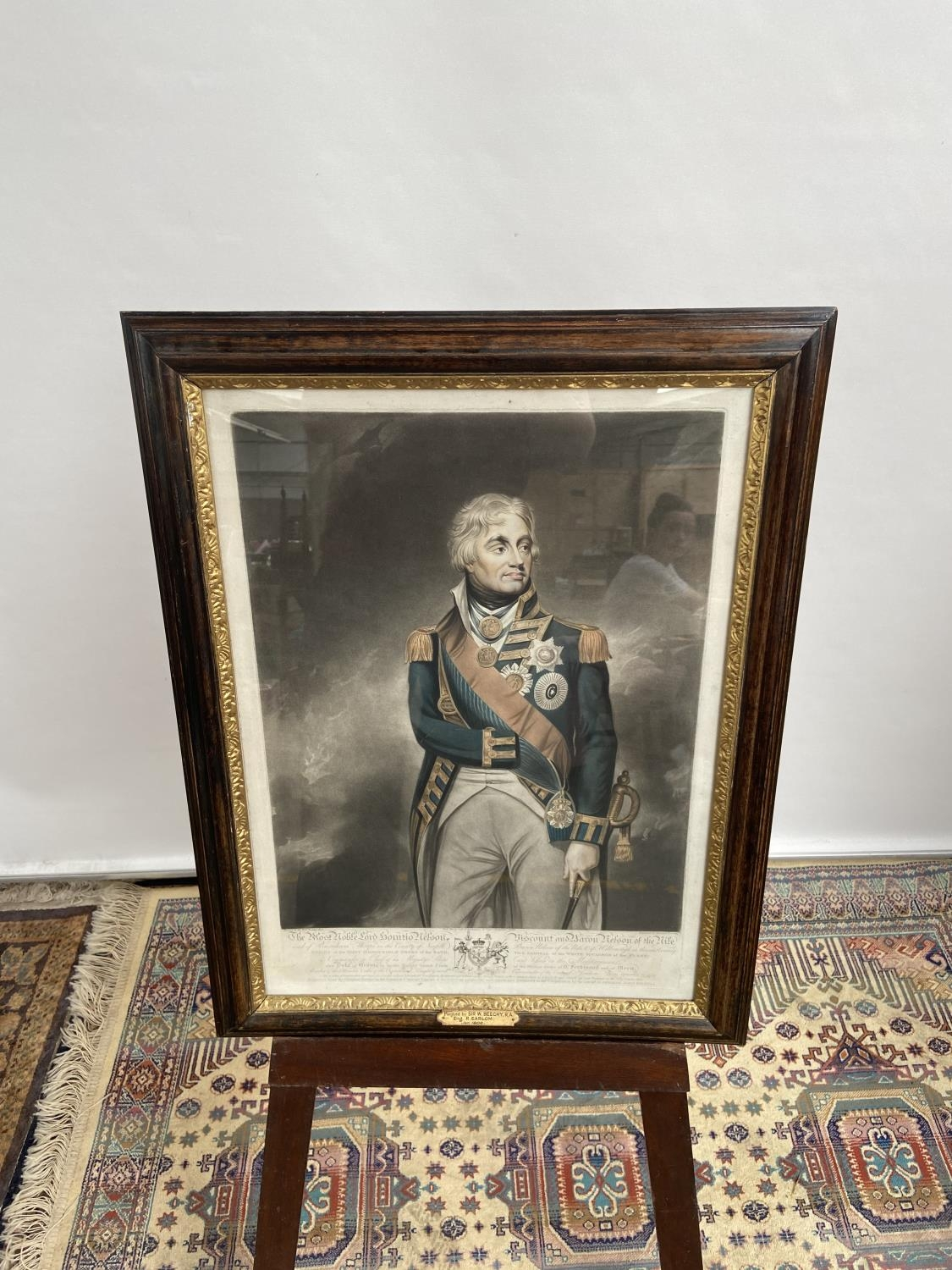 An early 19th century coloured engraving print of Lord Nelson, within a dark wood and gilt painted
