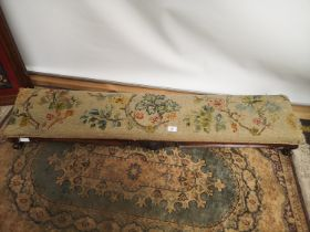 A Victorian fireside stool, upholstered with a foliage and floral tapestry design [length, 126cm,