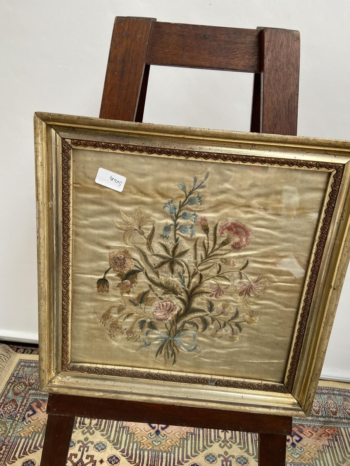 A 19th century silk tapestry depicting a bouquet of flowers, fitted within a gilt frame [height,