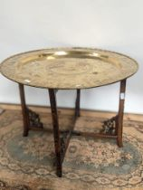 A 19th century gilt brass tea table, engraved with Chinese story sections, upon a hand carved