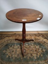 A Georgian pedestal table with circular top, supported on a tripod vase