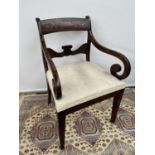 A Regency library chair, with scroll arm supports, upon tapered legs [height, 87cm, width 55cm]