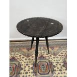 A hand carved hardwood oriental table, upon a tripod leg [height 48cm, diameter, 43cm]