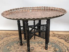 A 19th century middle eastern copper tea table, with an oval shape and detailed with engravings to