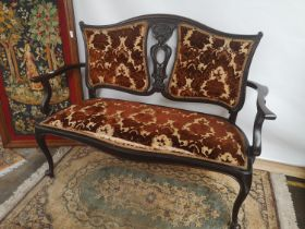 Late 19th/ early 20th century double chairback settee, with a centre carved splat, scroll arms and