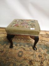 A Victorian square stool, supported on four Queen Anne legs, upholstered in a floral tapestry [