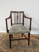 A Georgian arm chair, with channel carved arms, supported on tapered legs with a middle stretcher,
