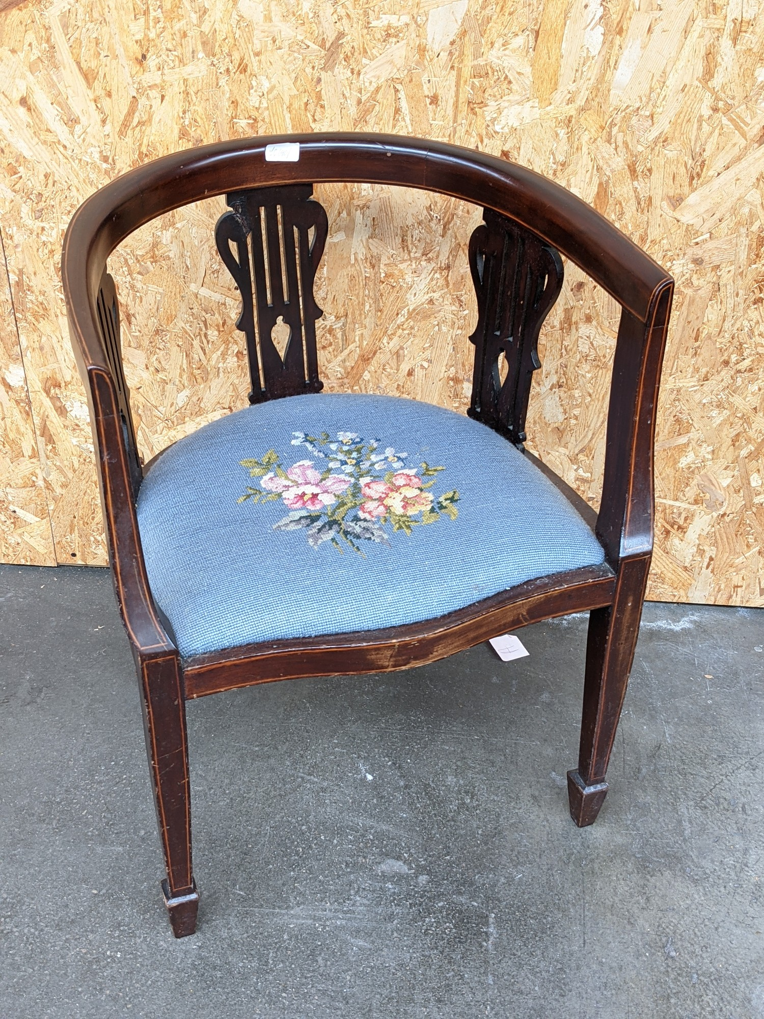 An Edwardian inlaid curved back arm chair, with three splat supports, upon pedestal legs,