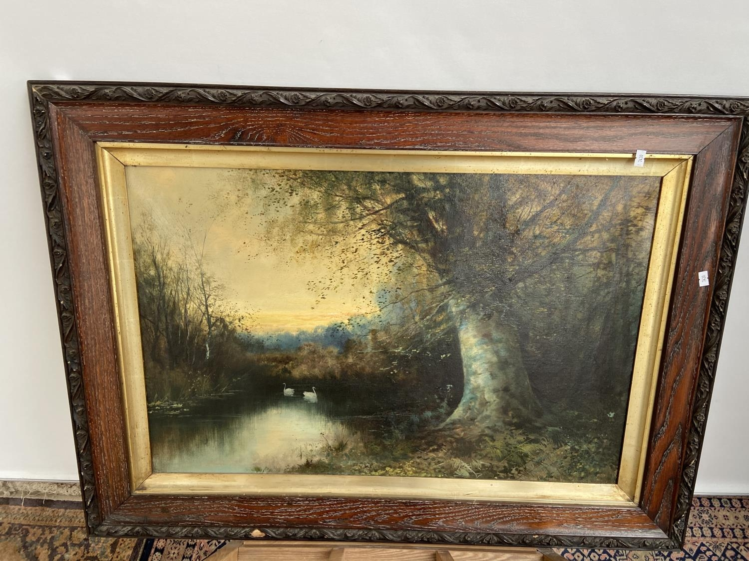 A 19th century oil painting on canvas depicting lake and forestry area scene. Fitted in a dark oak