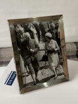 An original photograph of an elderly gentleman walking with Queen Elizabeth II. Fitted within a