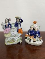Two various antique Staffordshire figurines to include clock design couple figurine and two gents