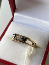 A 9ct gold sapphire & diamond ring set with a single bright white diamond [3mm] off set by two