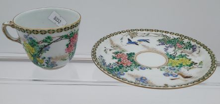 A 19th century Chinese cup and saucer, hand painted with flowers and birds.