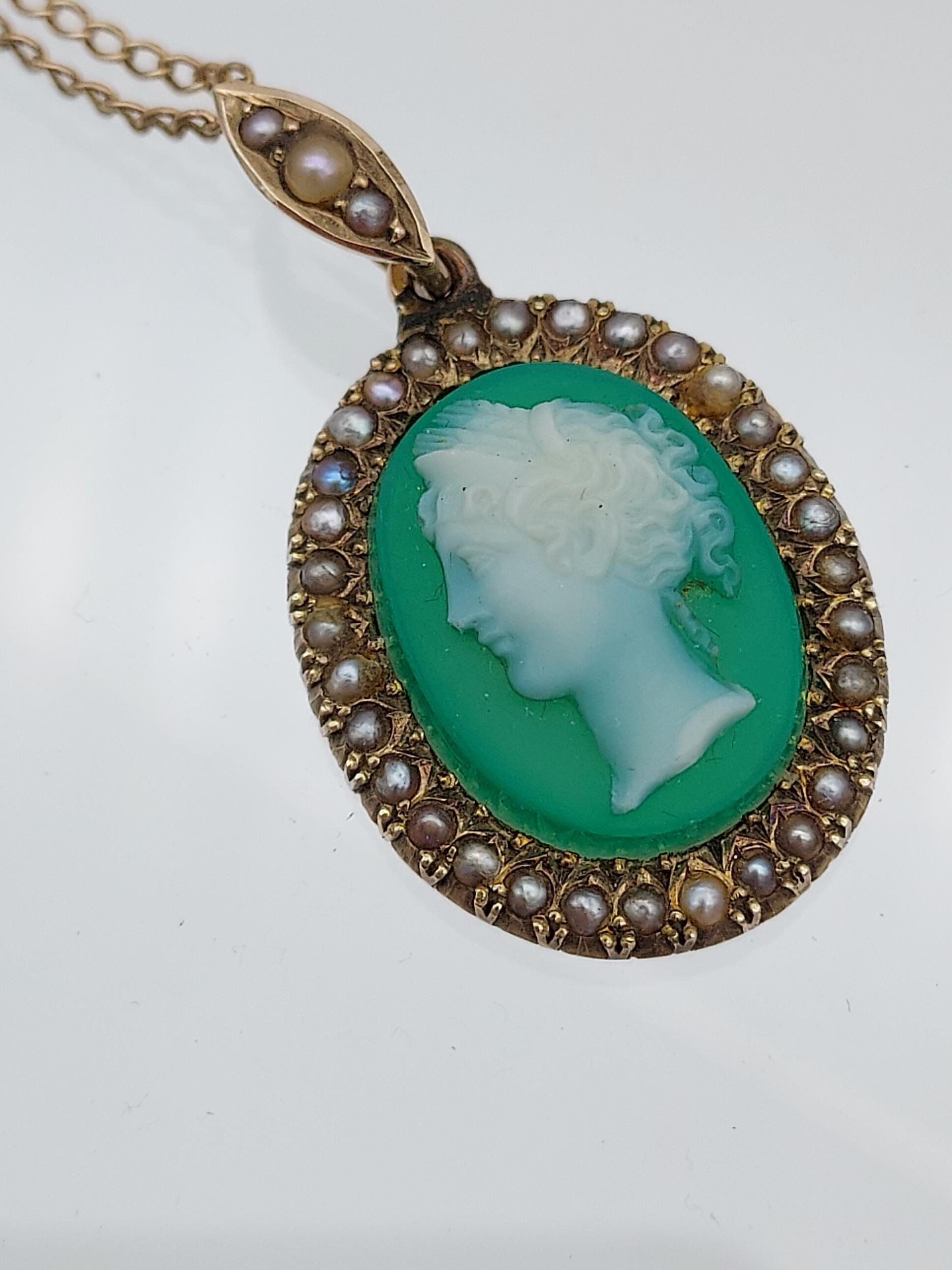 An early 1900's 9ct gold necklace with 9ct gold green cameo and seed pearl pendant.