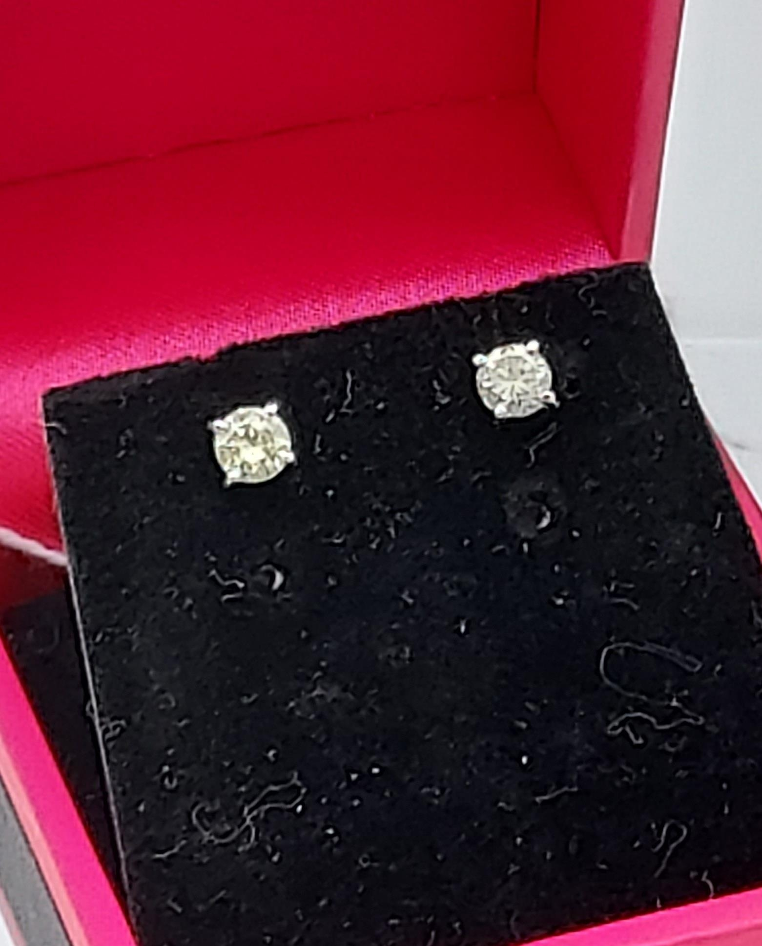 A pair of 14ct white gold diamond stud earrings [50] [0.61g]