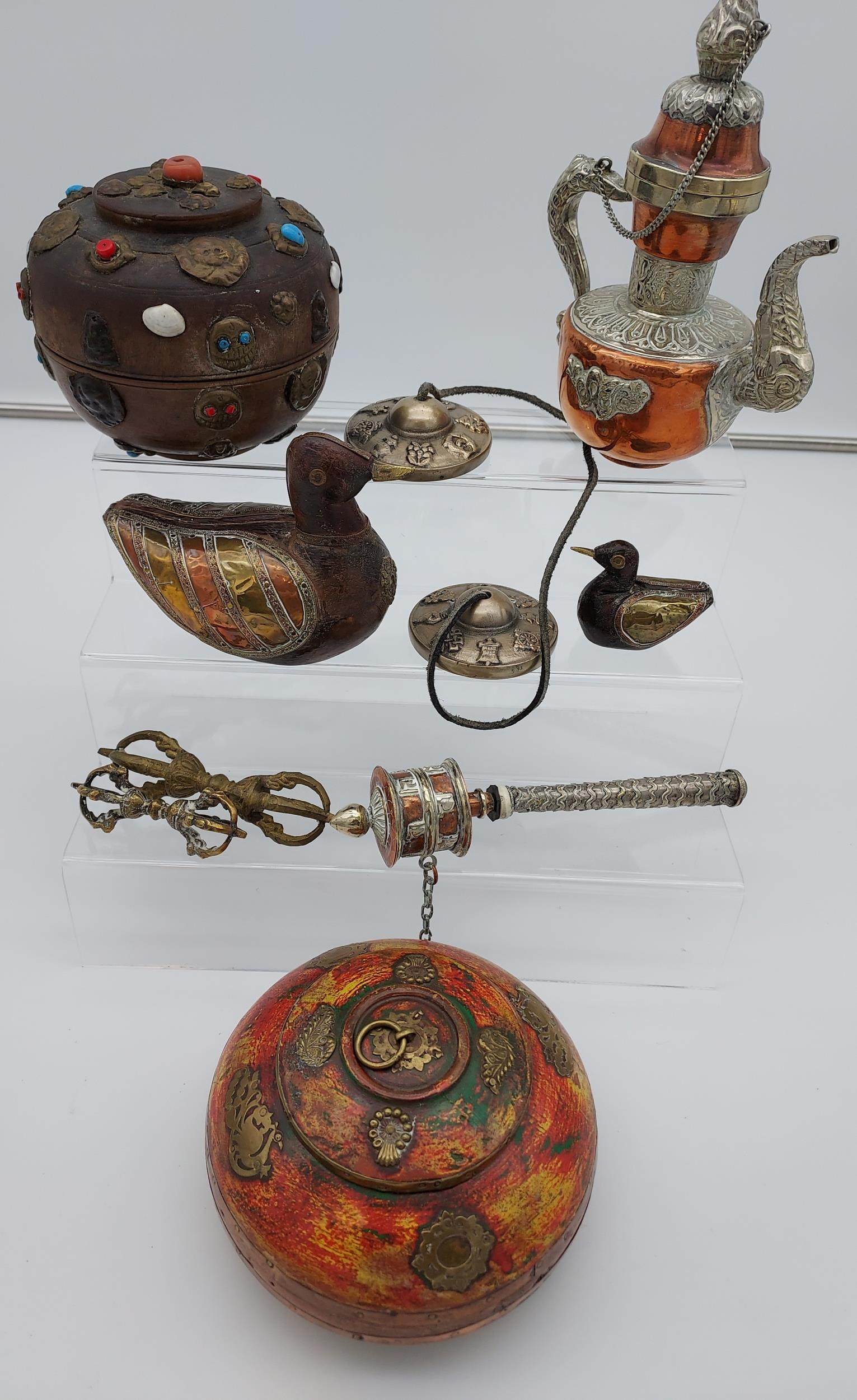 A collection of Tibetan antiques to include silver and copper teapot, prayer wheel, meditation chime