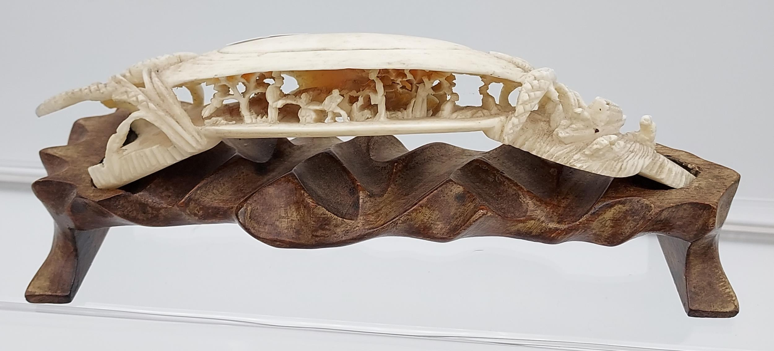 Antique Chinese hand carved ivory sculpture sat upon a carved wooden stand. [18cm in length]