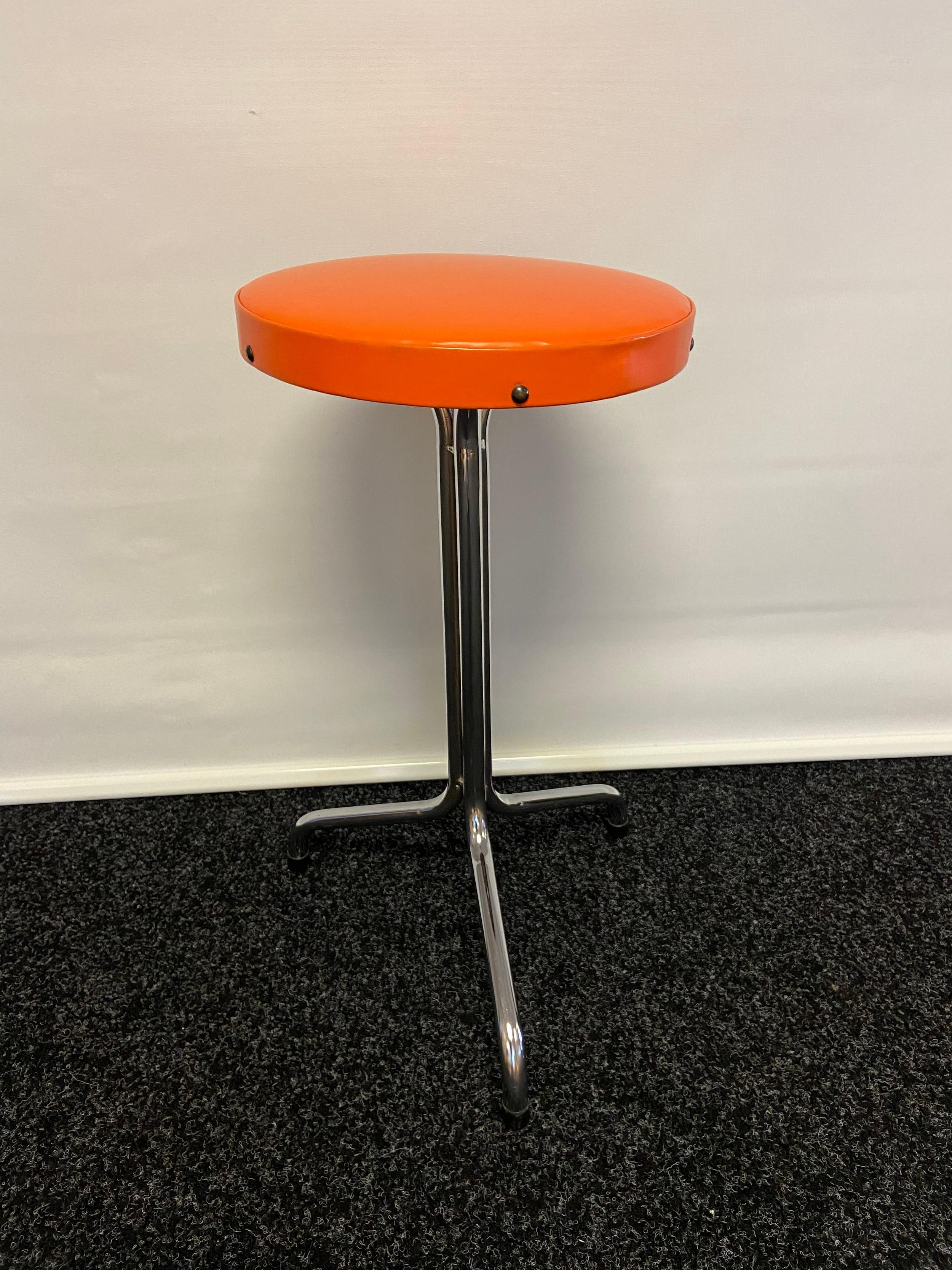 A Three legged mid century kitchen stool. Original orange covering [57cm]
