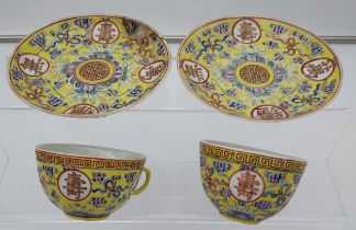 Two Chinese cups and saucers in a yellow ground, Guangxu 1875-1908 signature to the base.