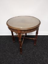 A 19th century barrel window table with glass top above a carved frieze,