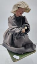 A 19th Century puppet of an elderly lady seated, Dated 1840. [32cm in height]