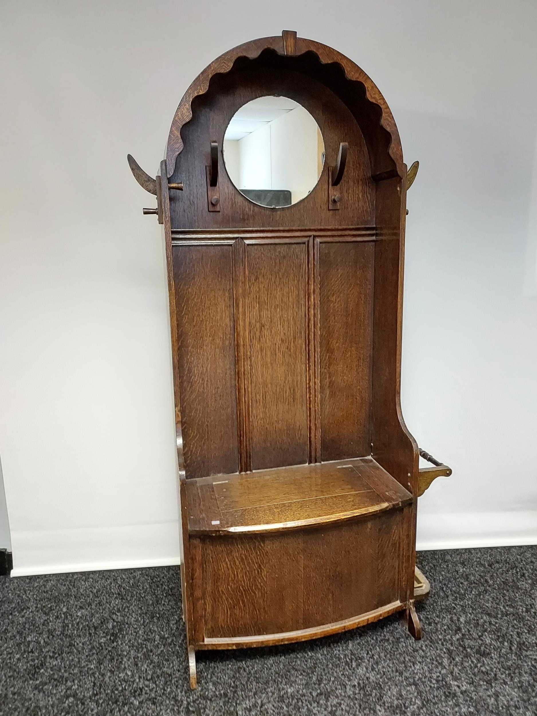 A nice example of an Art Deco oak, hall coat stand. Designed with a circular mirror, and lift up