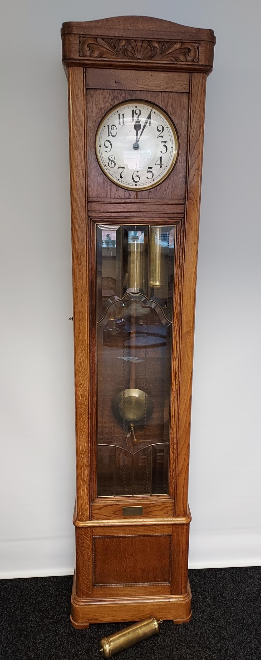 An oak cased Grandfather clock, with hand carved foliage design to the upper section, silver and