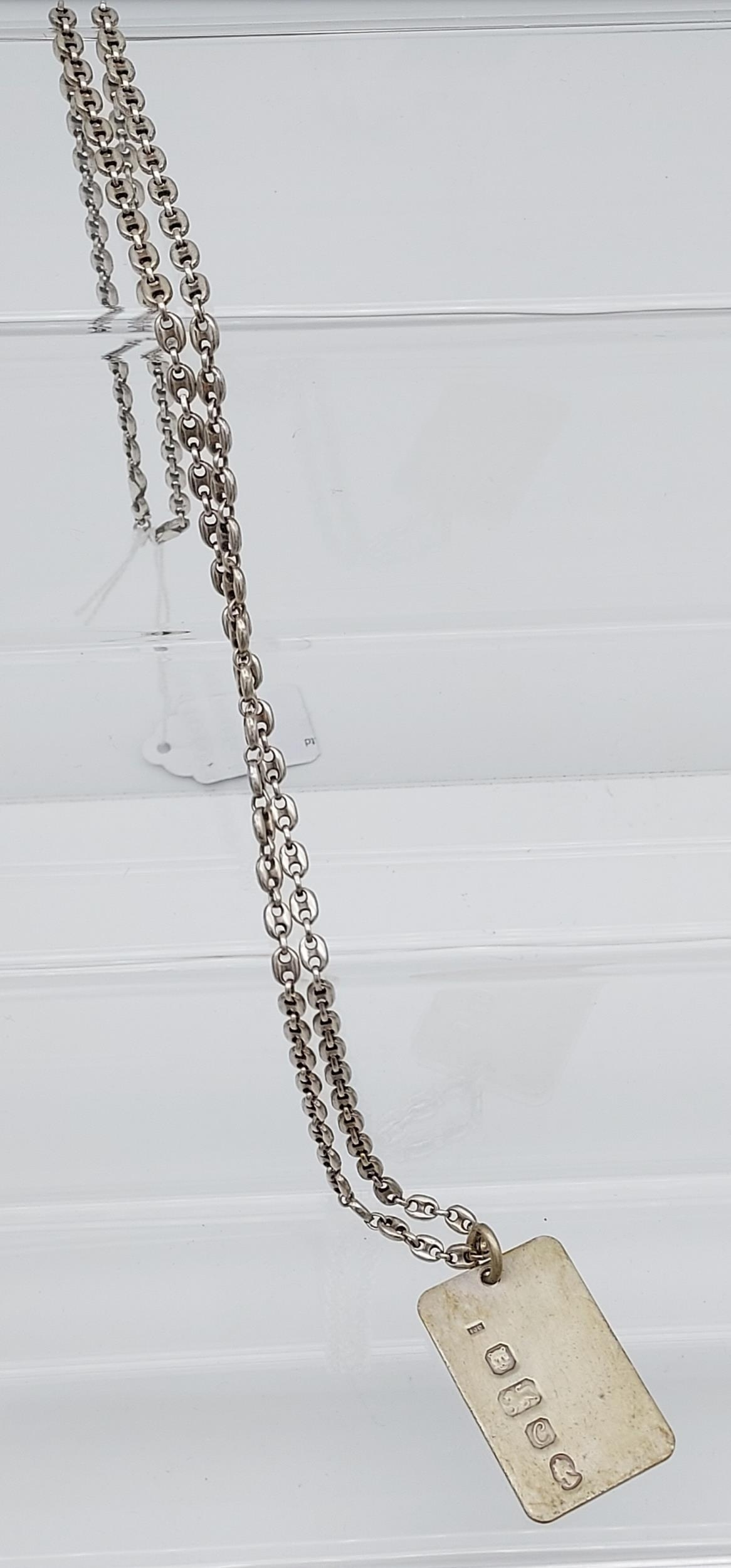 A London silver ingot with silver curb chain.