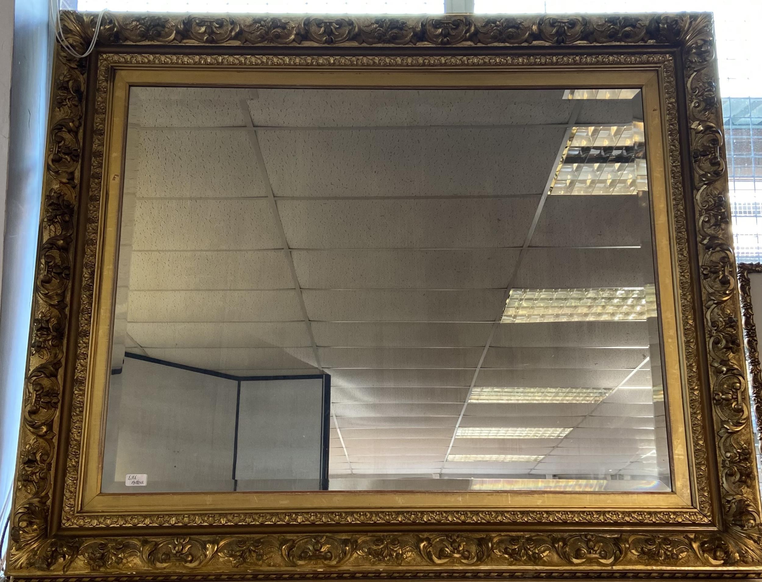 A Large impressive gilt framed and bevel edge mirror. [117x140cm]