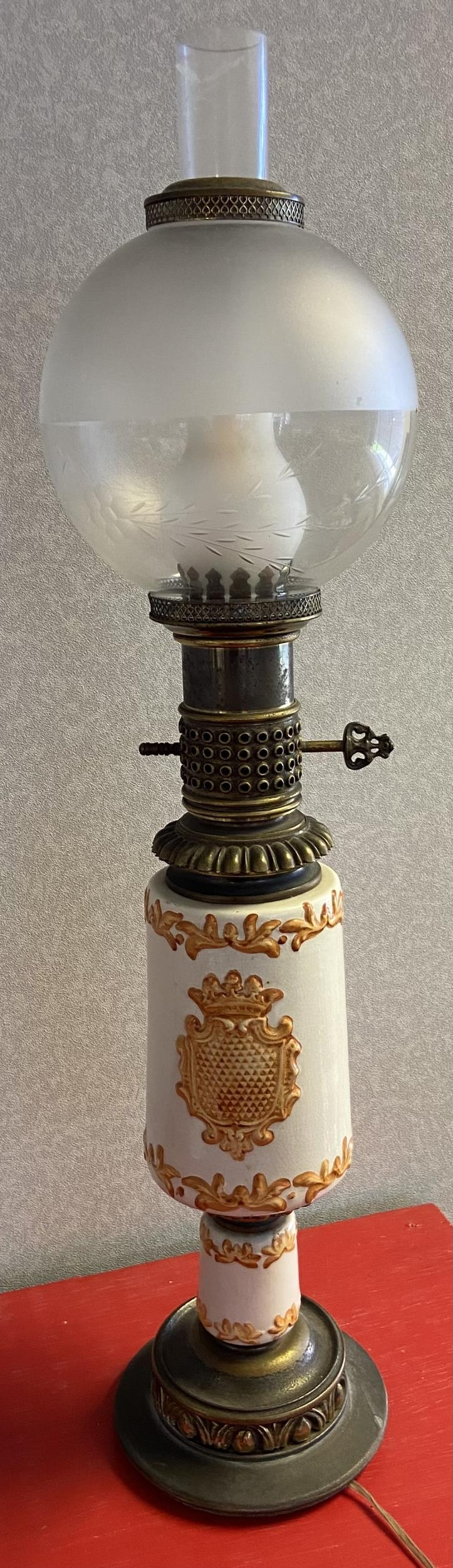 An Antique porcelain, metal and glass shade paraffin lamp converted to electric. [72cm in height]