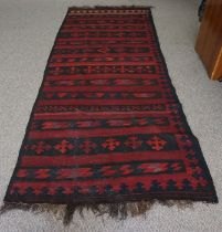 Turkish style Rug, Decorated with Geometric motifs on a red ground, 327cm x 133cm