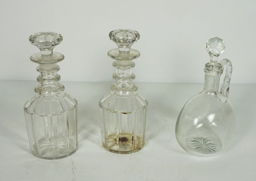 A pair of triple ring neck decanters and stoppers, 19th century, with paneled bodies, and a
