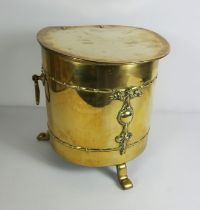 Brass Coal Depot, Early 20th century, Of cylindrical form with hinged cover, stylised feet, 31cm