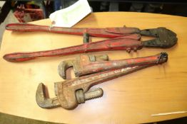 Two pipe wrenches and a bolt cutter