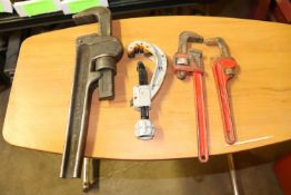 Three pipe wrenches and a pipe cutter