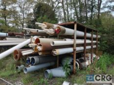 Lot of assorted pipe including steel, stainless, ABS, and PVC on racks, includes racks (Laydown