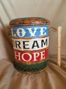 """""""LOVE, DREAM, HOPE"""" GARDEN OTTOMAN This ottoman is made out of metal and has a padded top for"""