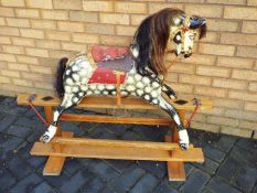 A good quality early 20th century rocking horse on glider base, painted dapple body with open mouth,