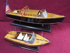 Two static wooden display models of Riva type luxury yachts.