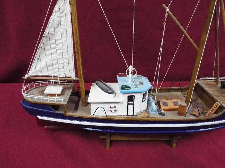 A static wooden model of a fishing vessel on a stand. - Image 3 of 4