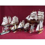 A flotilla of ten static wooden models on stands depicting fishing vessels,