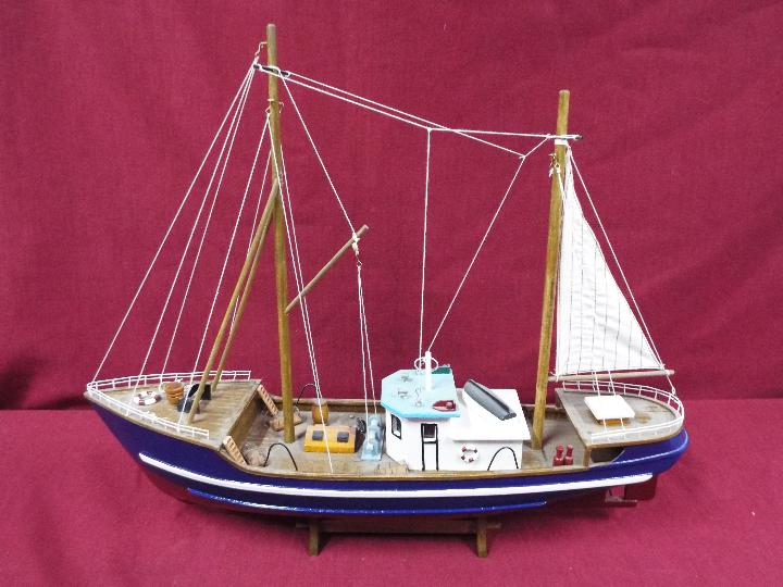 A static wooden model of a fishing vessel on a stand. - Image 4 of 4