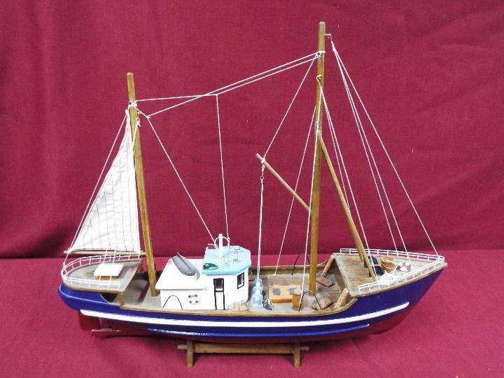 A static wooden model of a fishing vessel on a stand.