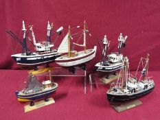 A flotilla of five static wooden models on stands depicting fishing vessels.