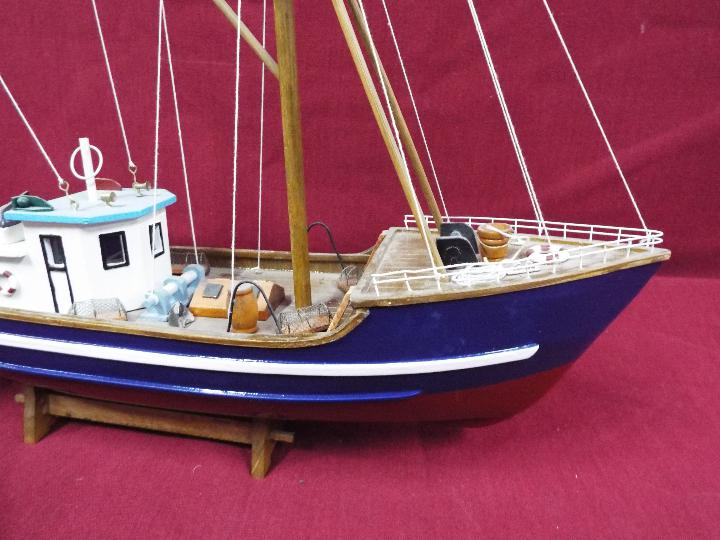 A static wooden model of a fishing vessel on a stand. - Image 2 of 4