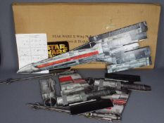 Star Wars - A large cardboard X Wing Fighter mobile shop display in its original shipping box dated