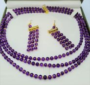 A three row amethyst necklace and matching earrings set in a presentation box. Necklace length: 47 -