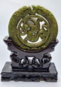 A Chinese carved green jade disc (amulet?) with mythical beasts on a custom made wooden base. Disc