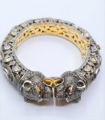 An antique Cartier style yellow and white gold tigers head bangle encrusted with diamonds and